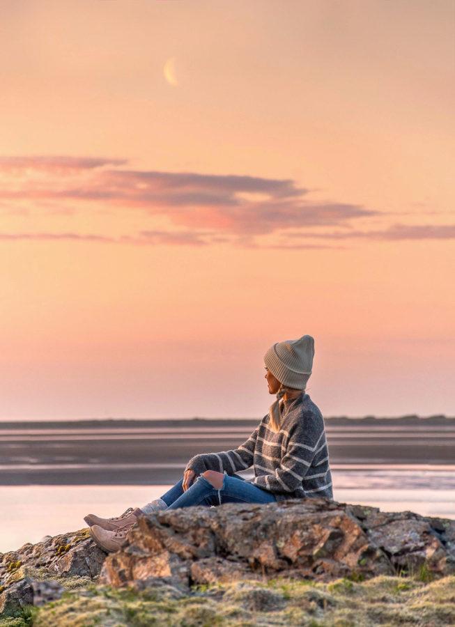 Frau sitzt beim Sonnenuntergang in schöner Landschaft auf Island