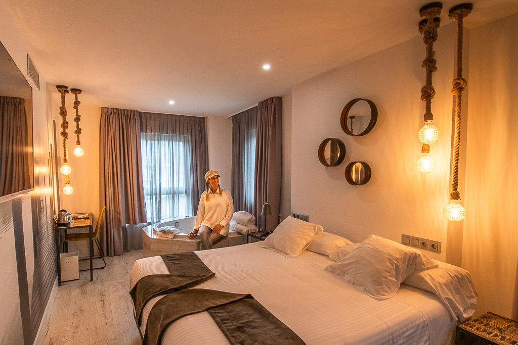 Frau sitzt in hell beleuchtetem Hotelzimmer