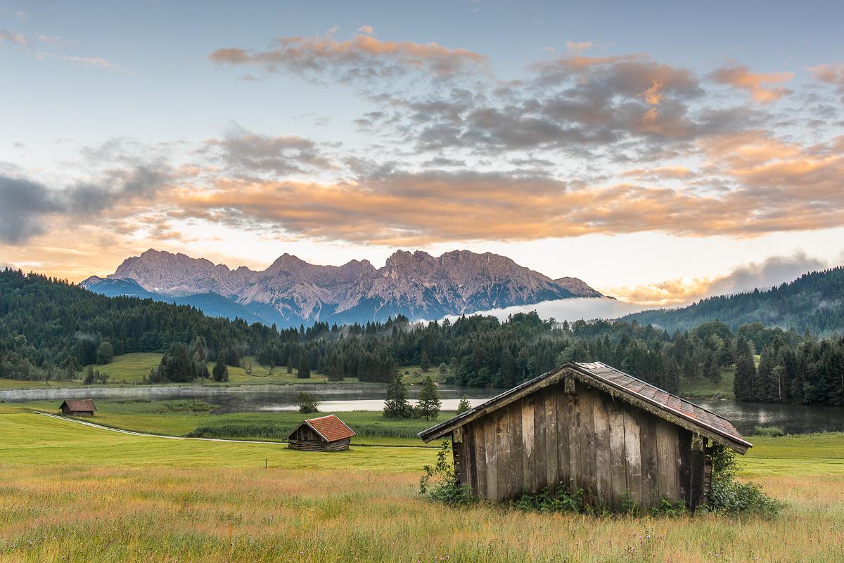 Holzhütte vor einem großen See vor großen Bergen in Bayern