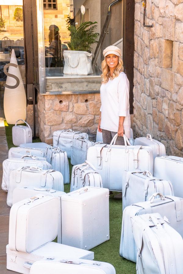 Frau steht mit vielen Koffern vor einem Hotel