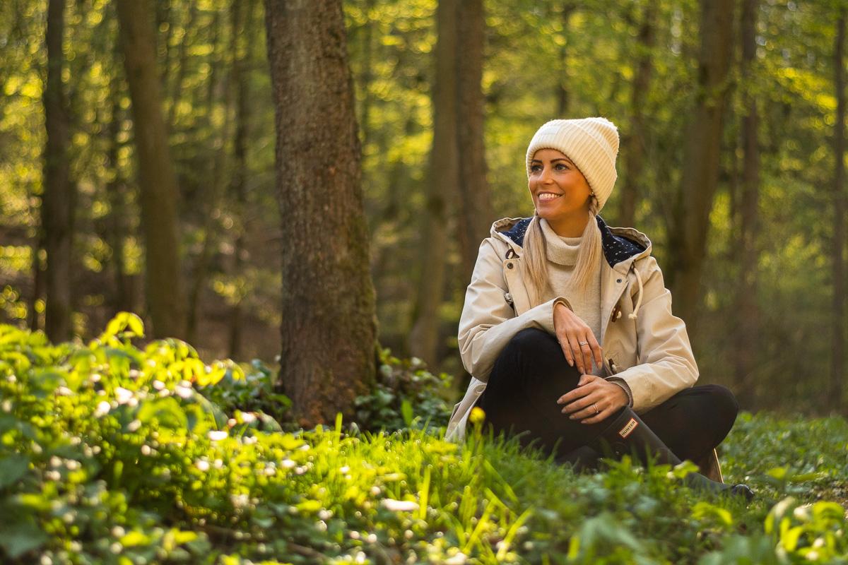 Frau sitzt in idyllischem Wald