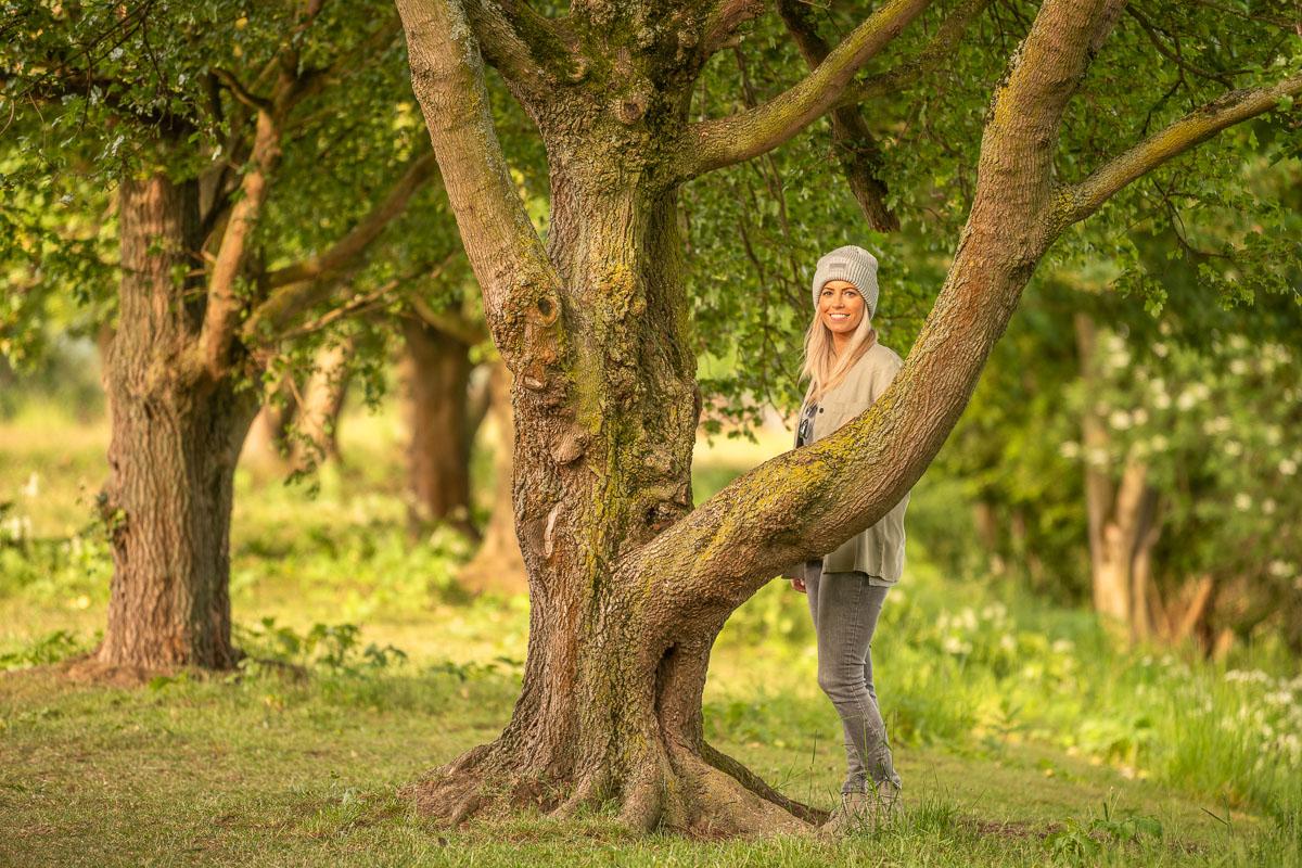 Frau steht hinter einem Baum im Grünen am Kemnader See im Ruhrgebiet