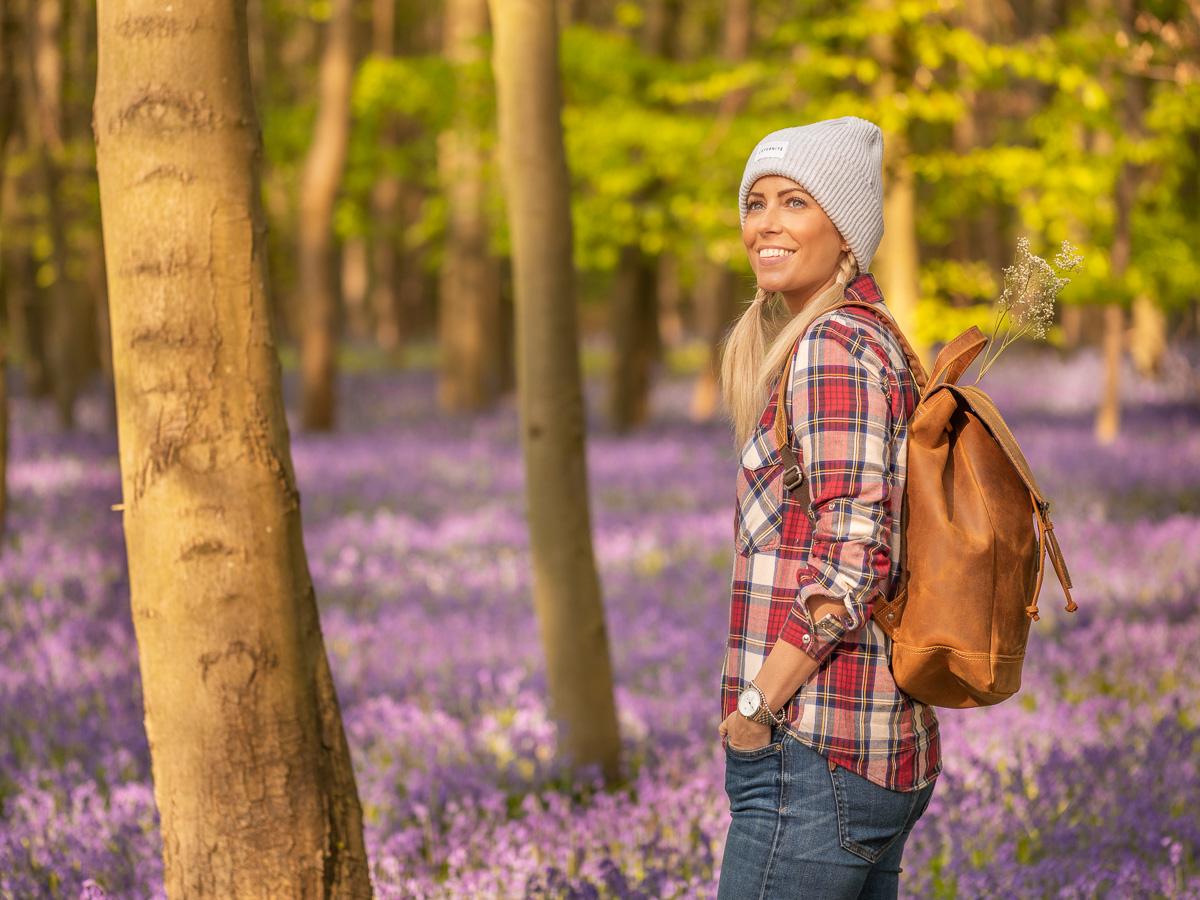Frau steht im Wald mit blauen Blumen