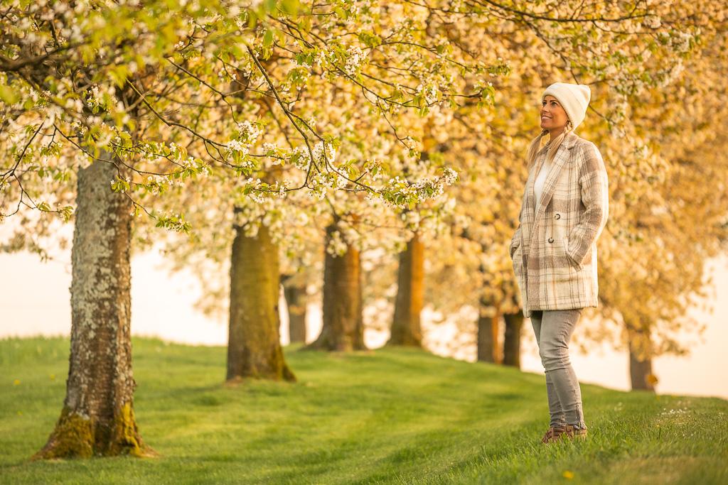 Frau steht am Rande einer Baumreihe und schaut in die Baumkrone
