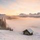 Zwei Holzhütten im Schnee mit dichtem Nebel im Hintergrund