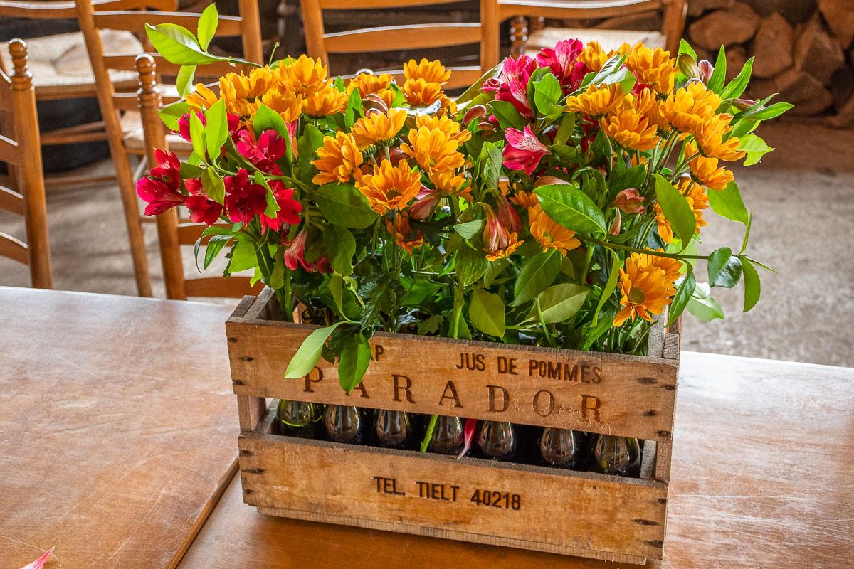 Bunter Blumenkorb steht auf einem hölzernen Tisch