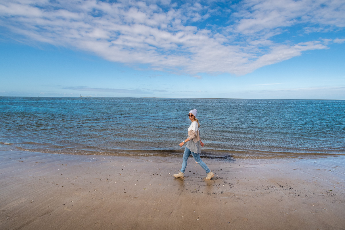 Frau geht an der Nordsee entlang