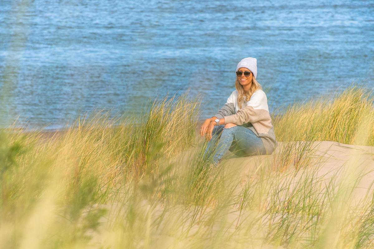 Frau sitzt in Dünen auf weißem Sandstrand an der Nordsee