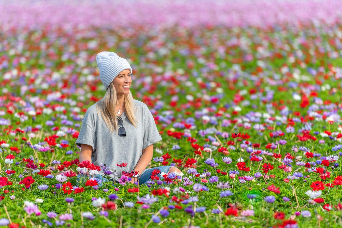 Frau sitzt in einem Meer von bunten Blumen