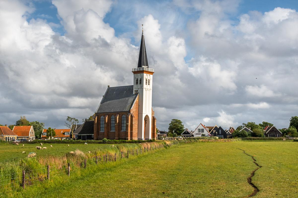Hübsche Kirche vor einer saftig grünen Wiese auf Texel