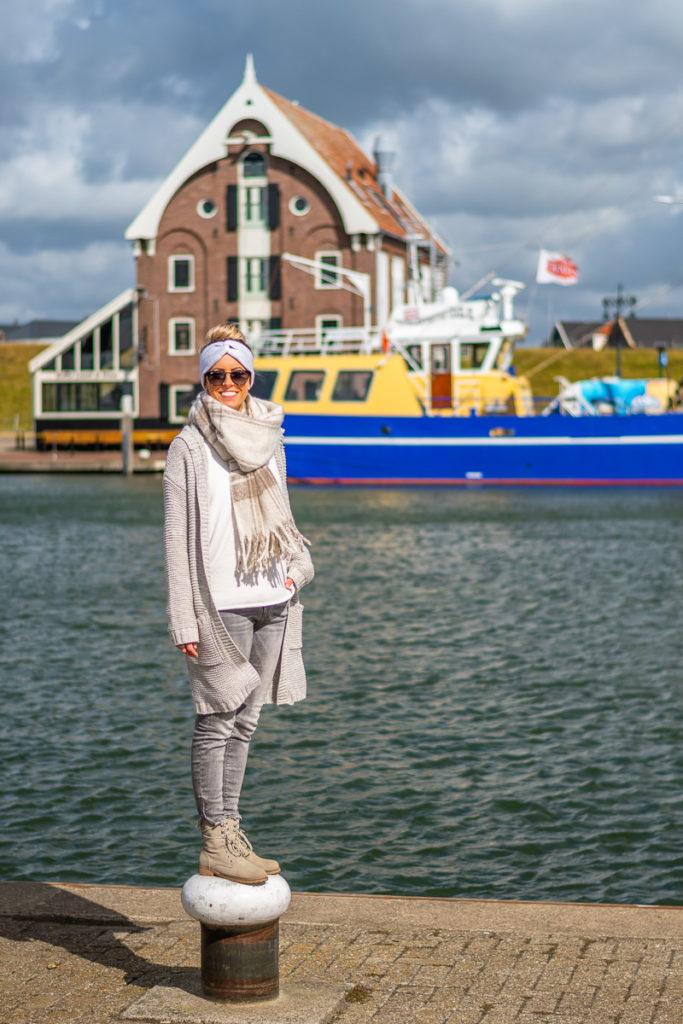 Frau steht am Hafen der Nordsee auf Texel