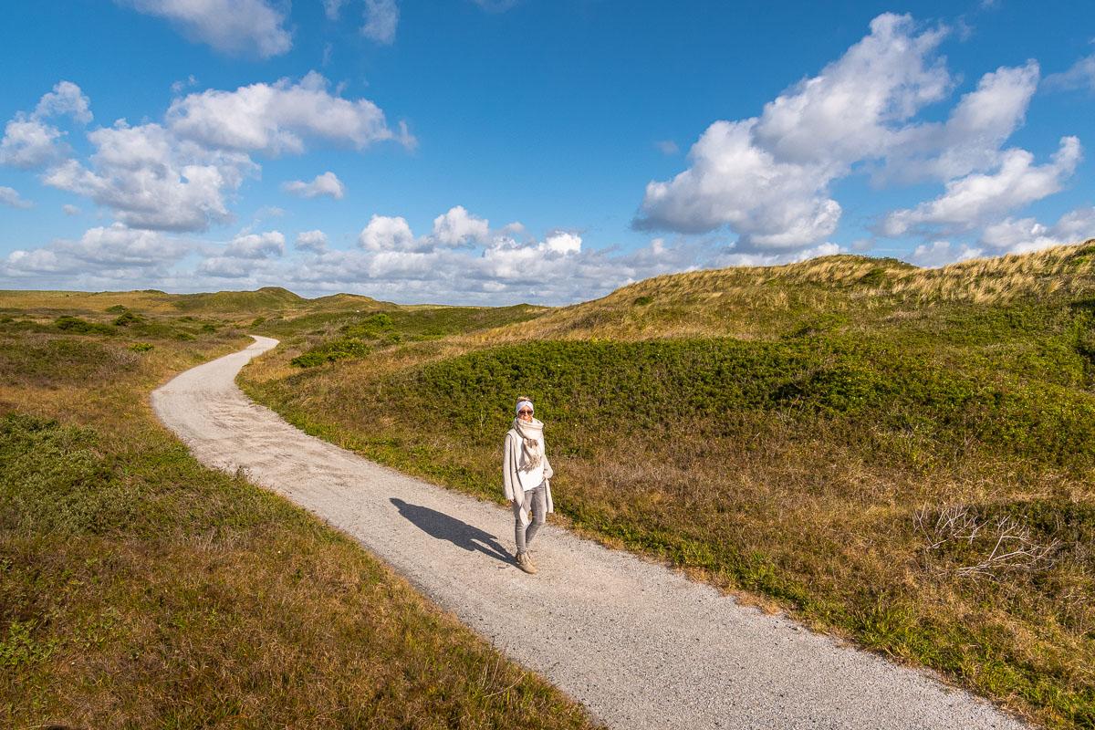 Frau schlendert über einen Weg auf Texel in der Sonne