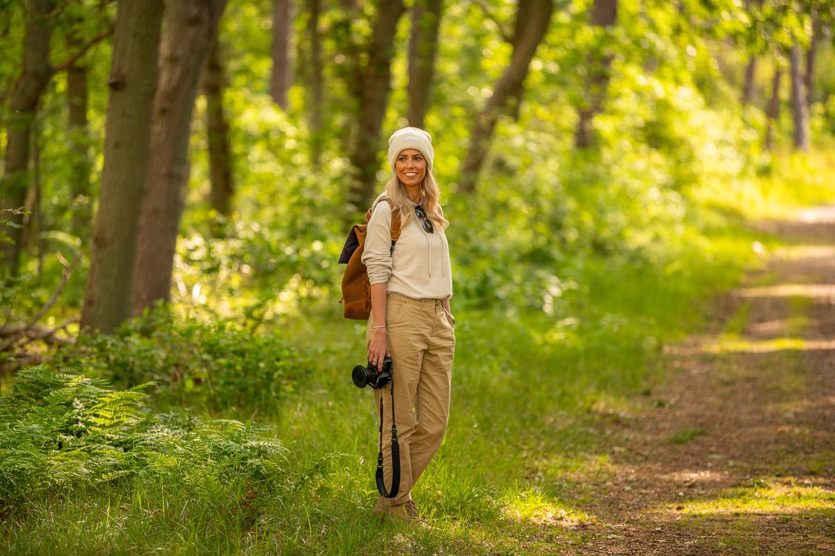 Frau steht mit Kamera in einem grünen, hellen Wald auf Texel