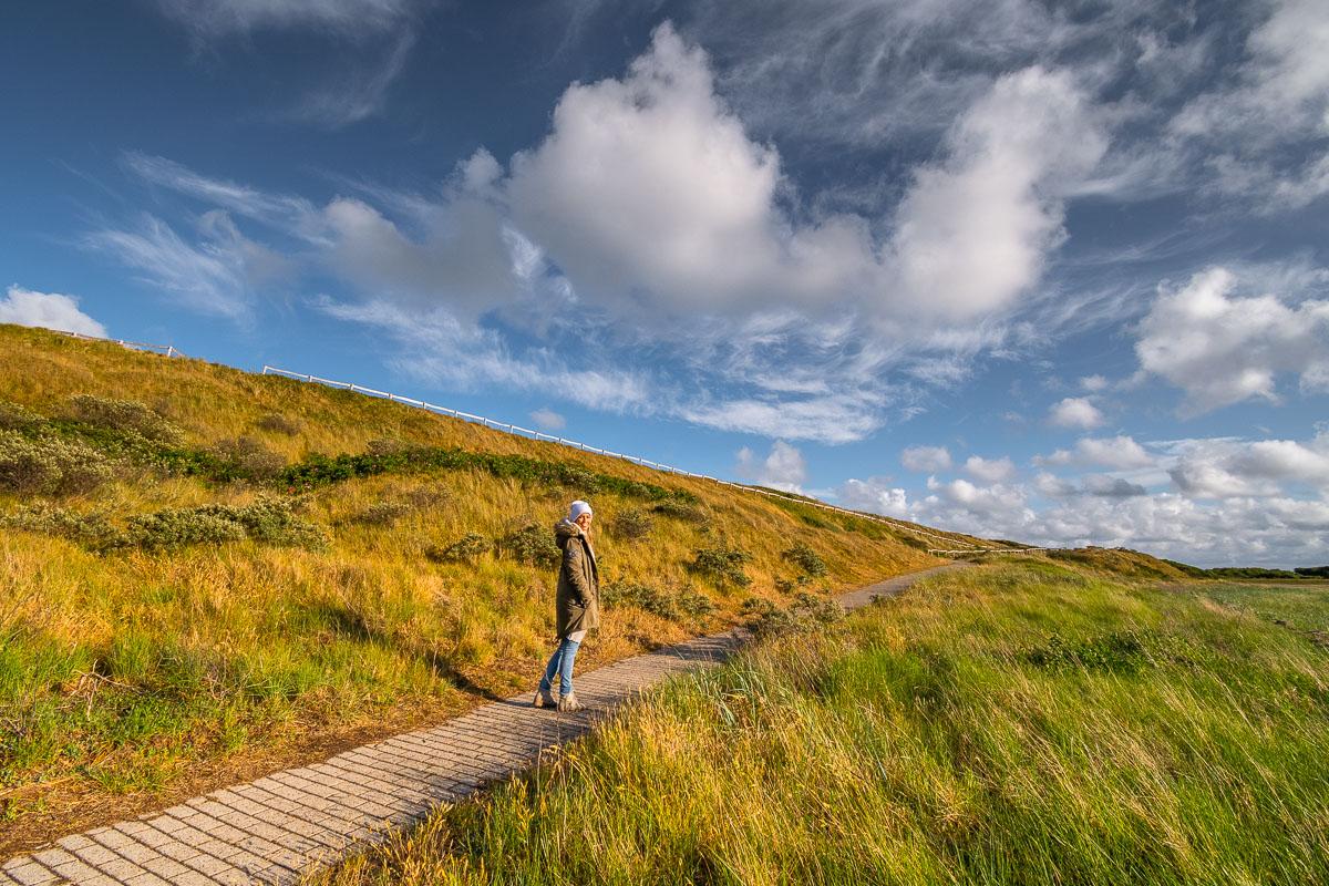 Frau wandert durch ein grünes Gebiet auf Texel