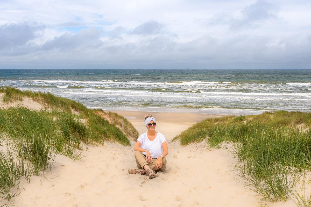 Frau sitzt am Strand der Nordsee auf Texel