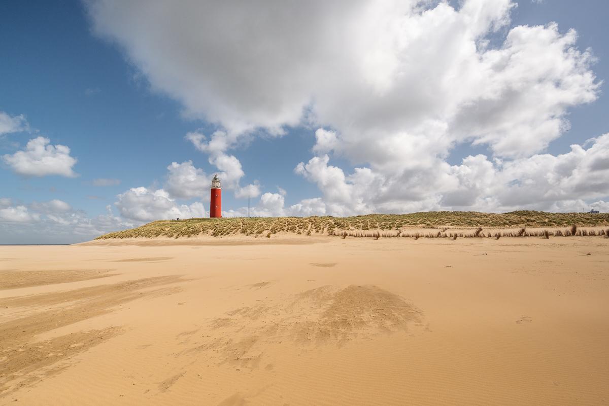 Weißer Sandstrand mit einem roten Leuchtturm im Hintergrund