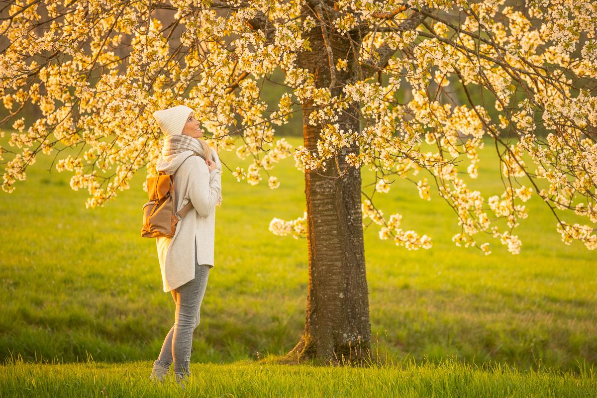 Frau schaut in einen Baum hinein