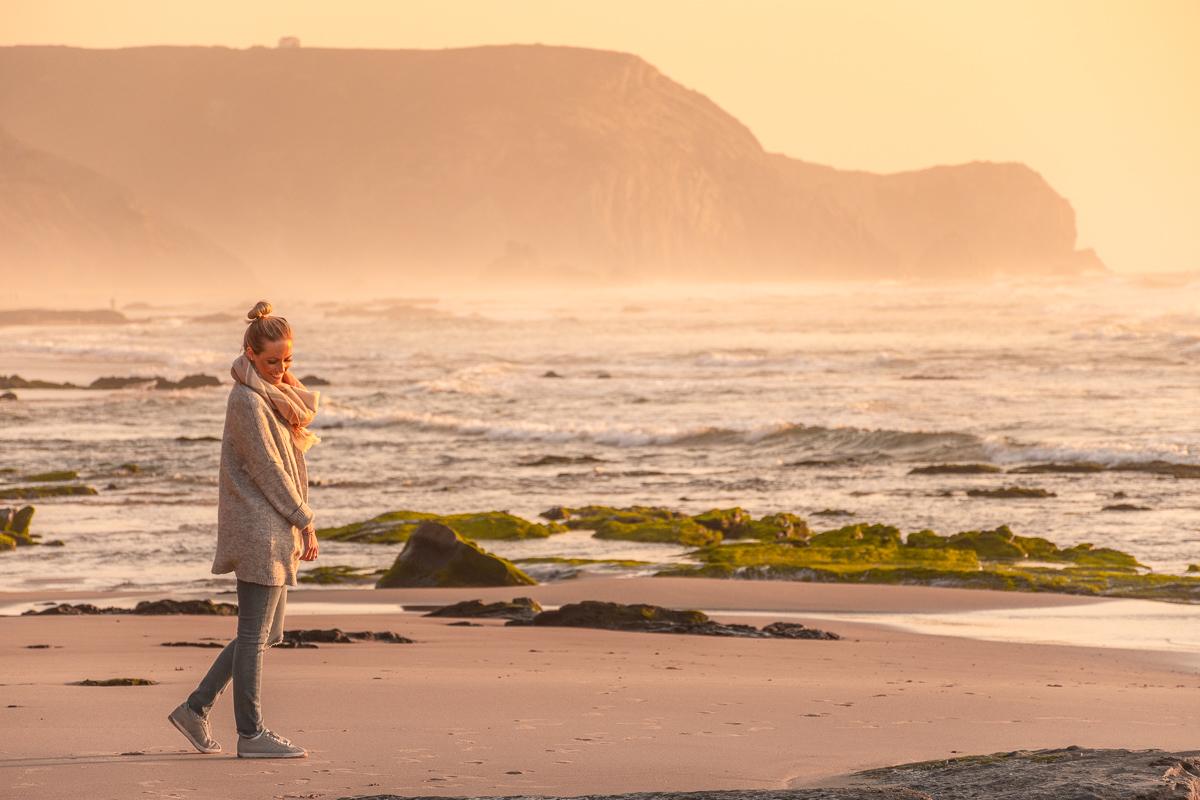 Frau steht am Strand und denkt an den Urlaubsblues