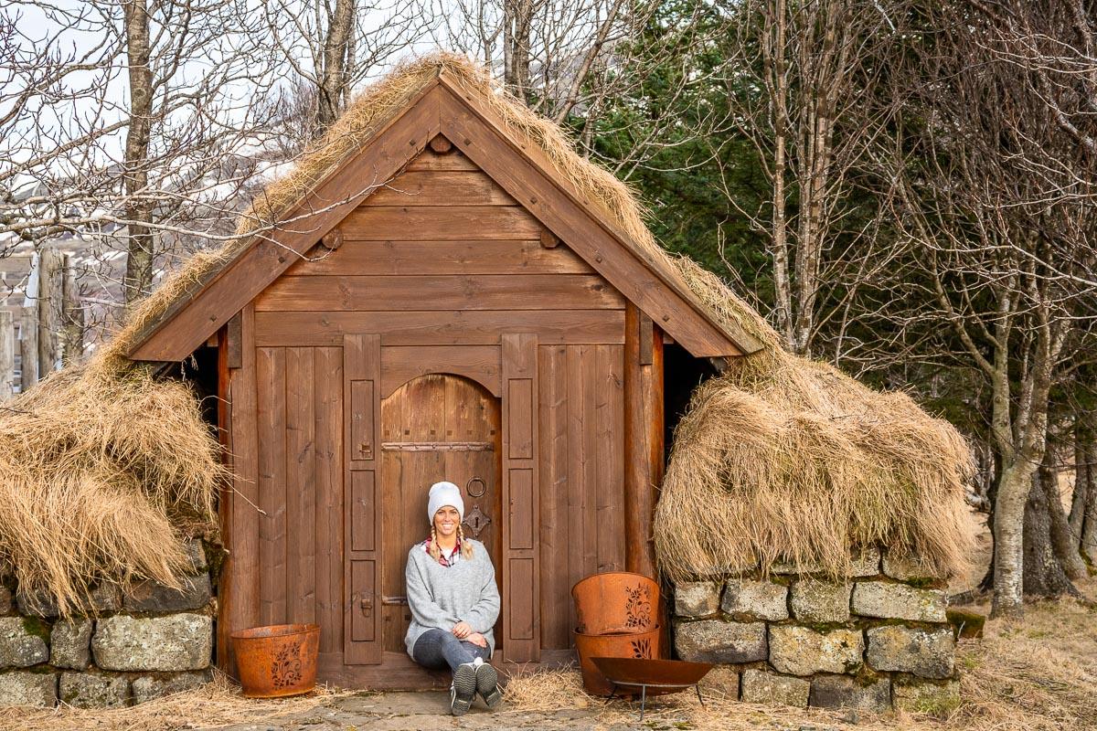 Frau sitzt vor einer Holzhütte und denkt an das Ende der Reise