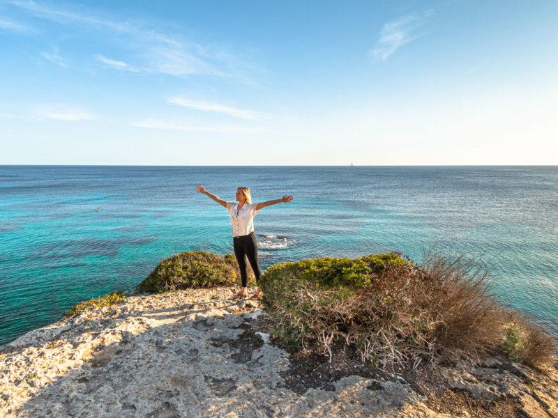 Frau steht auf einem Felsen und blickt auf das Meer-Urlaubsblues
