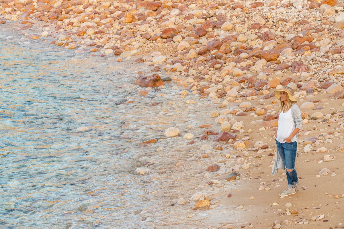 Frau steht am Strand mit vielen Steinen und denkt an den Urlaubsblues