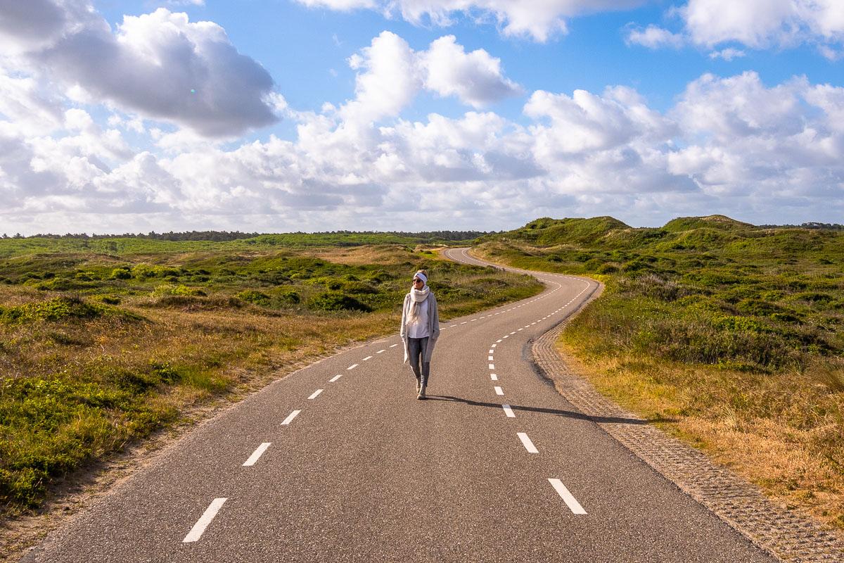 Frau schlendert über Straße und denkt an den Urlaubsblues