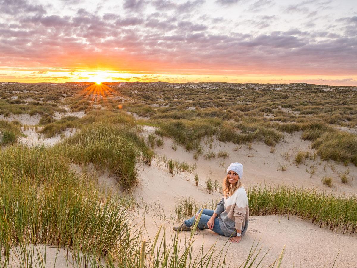 Frau sitzt beim Sonnenuntergang in einer Dünenlandschaft auf Texek