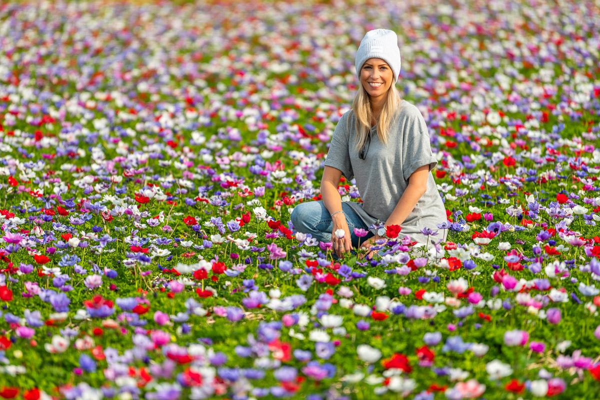 Frau sitzt in einer bunten Blumenwiese auf Texel