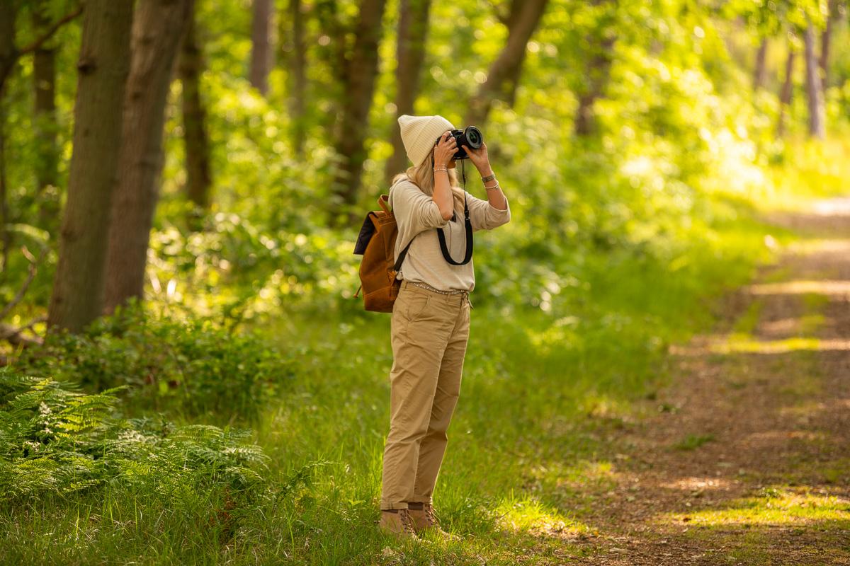 Frau steht im Wald und fotografiert Bäume auf Texel