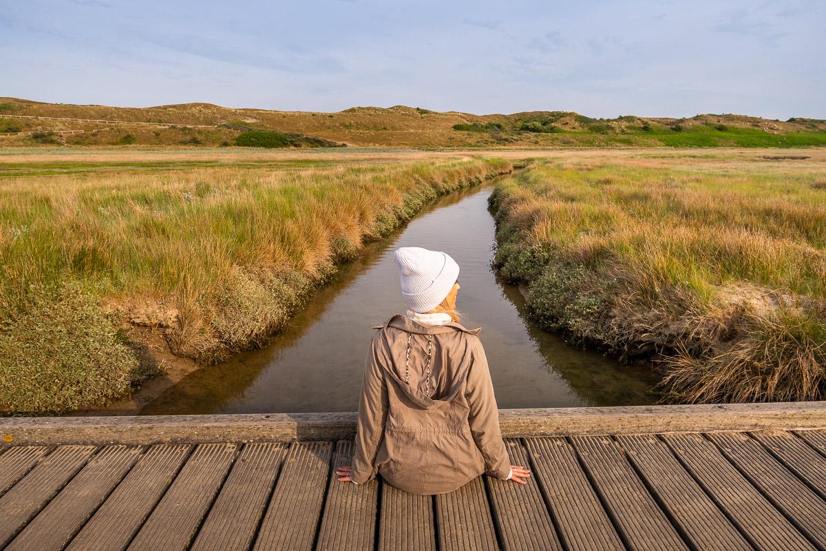 Frau sitzt auf kleiner Brück und schaut auf einen Salzpriel im De Slufter