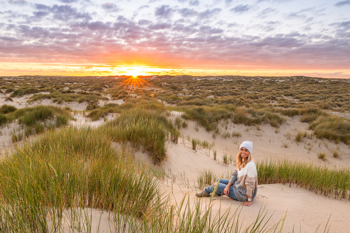 Frau sitzt in den Dünen vor dem Sonnenuntergang