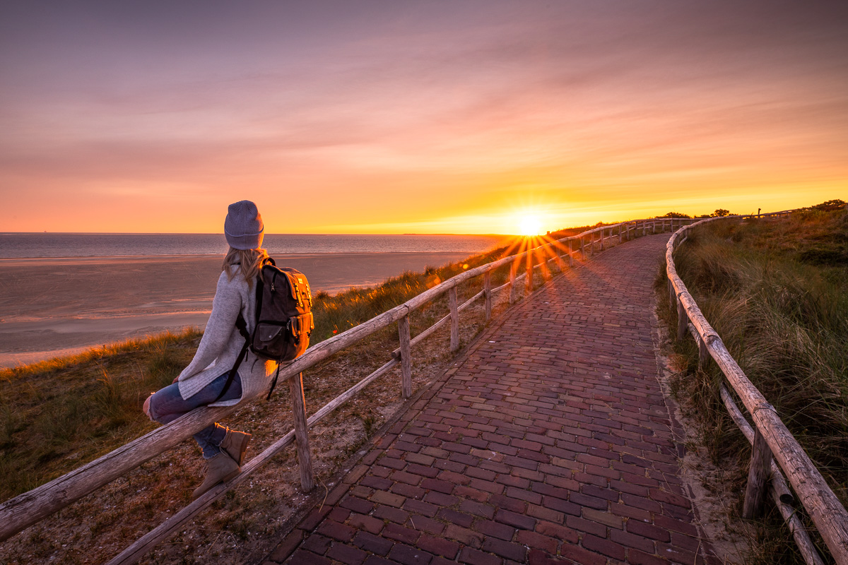 Frau schaut sich den Sonnenaufgang am Leuchtturm von Texel an