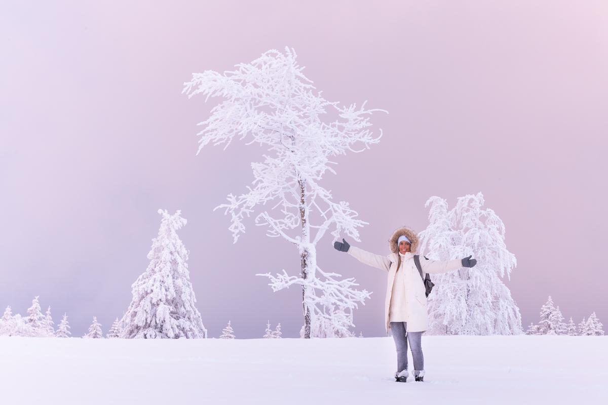 Frau steht im rosa Abendlicht im Schnee