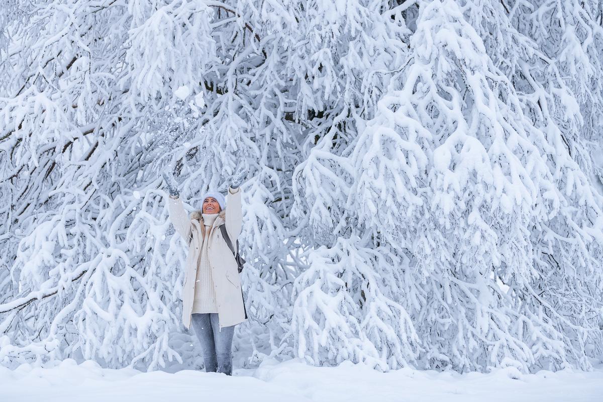 Frau wirft lachend Schnee in die Luft