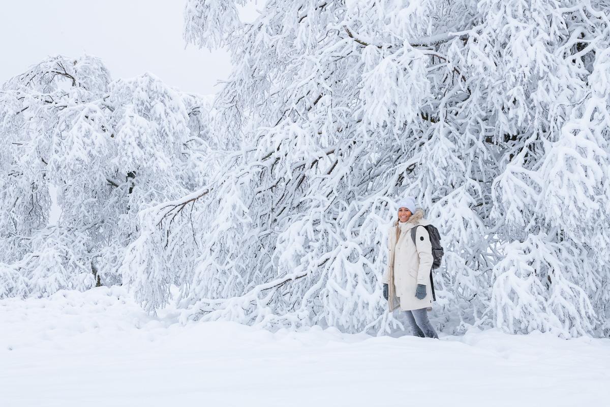 Frau steht vor schneebedeckten Baeumen