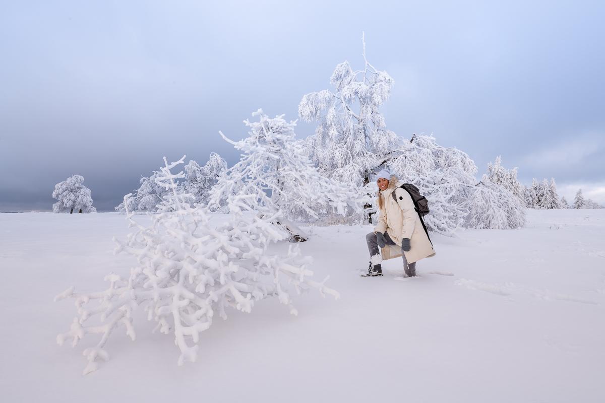 Frau kniet im tiefen Schnee
