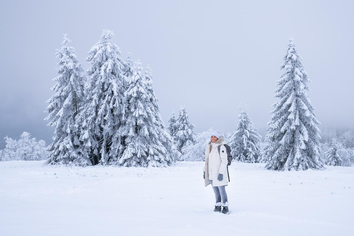 Frau steht in einer Schneelandschaft