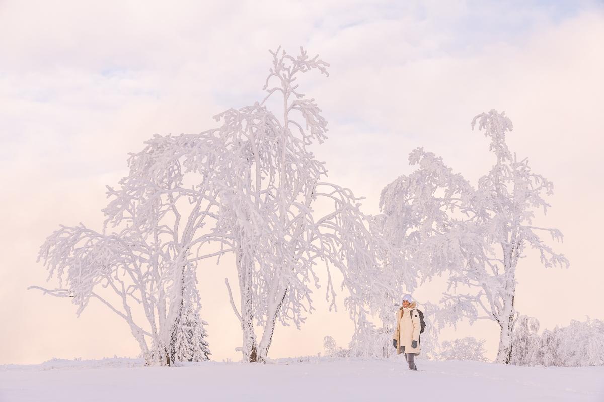 Eine Frau steht im Abendlicht im Schnee