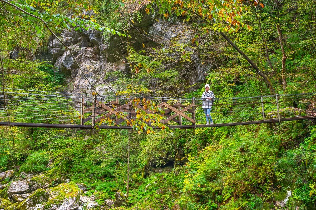 Frau steht auf hölzernen Hängebrücke im Soca Tal
