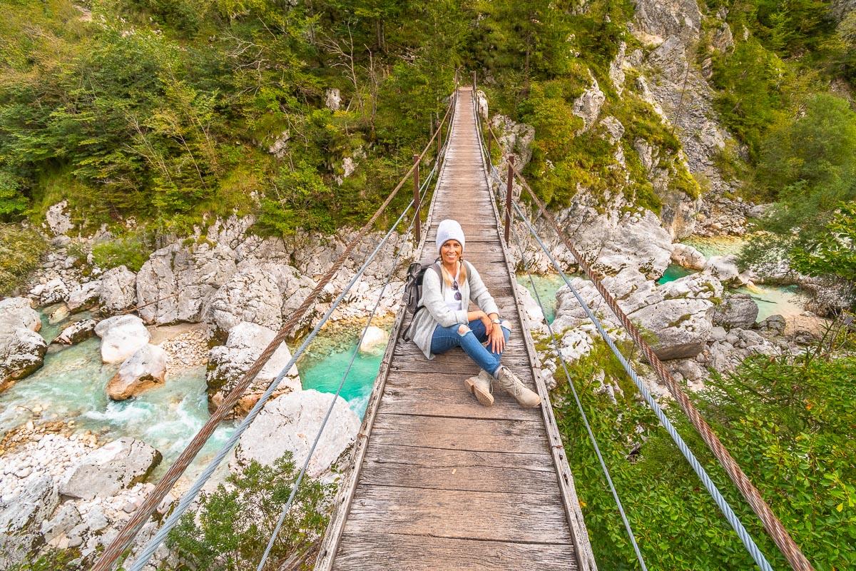 Frau sitzt auf Hängebrücke im Socatal in Slowenien