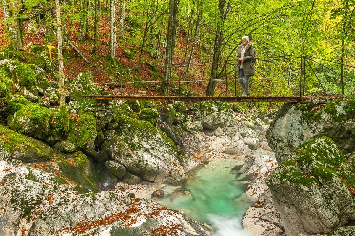 Frau steht auf einer Hängebrücke im Socatal