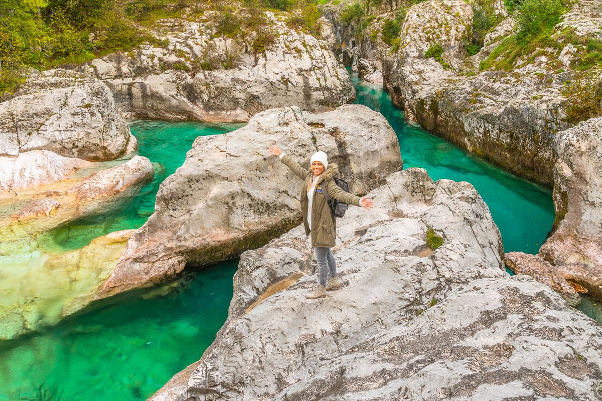 Frau steht im Socatal in Slowenien vor türkisem Wasser
