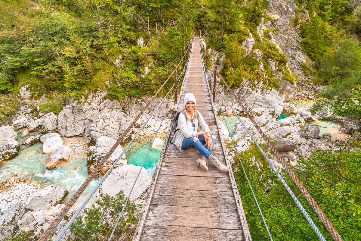 Frau sitzt auf Hängebrücke im Soca Tal