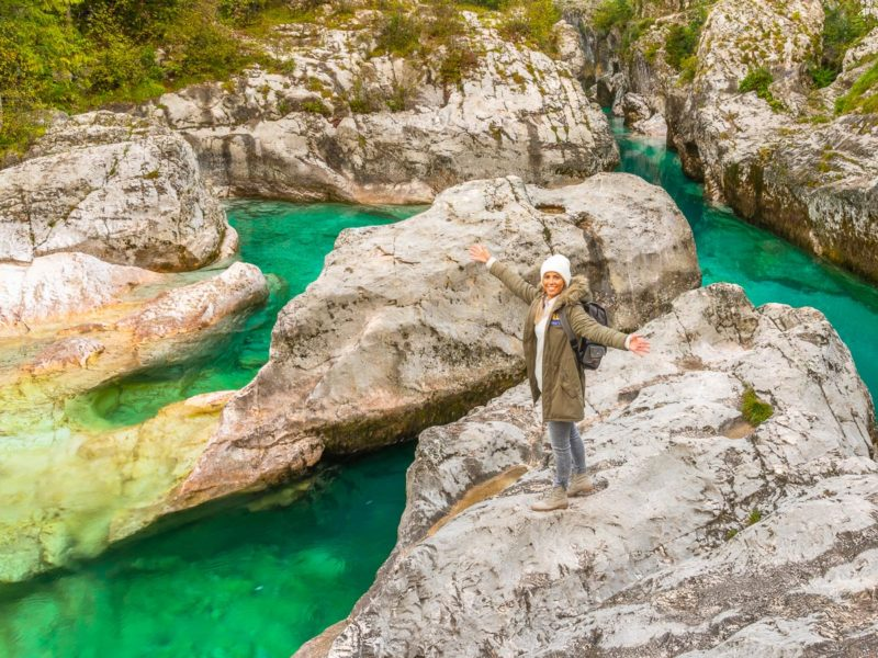 Frau steht auf einem hellen Felsen neben einem türkisen Fluss