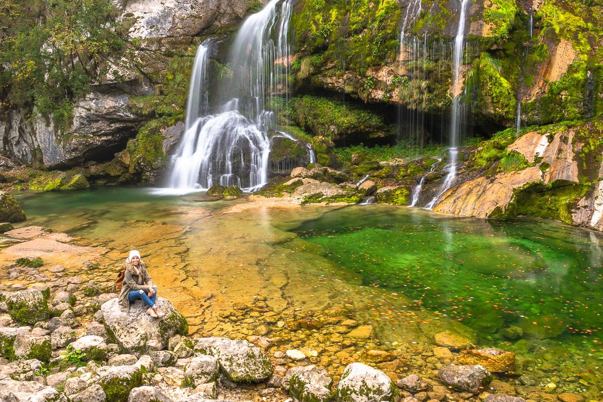 Frau sitzt vor einem Wasserfall im Soca Tal