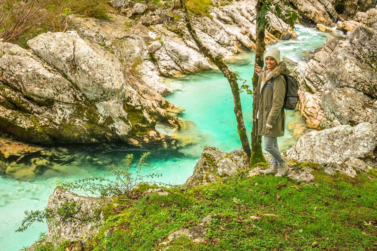 Frau steht an dem Fluss Soca in Slowenien